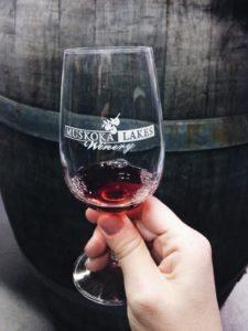 glass with Muskoka Lakes Winery logo in front of an oak barrel