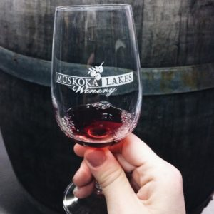 glass with Muskoka Lakes Winery logo in front of an oak barrel