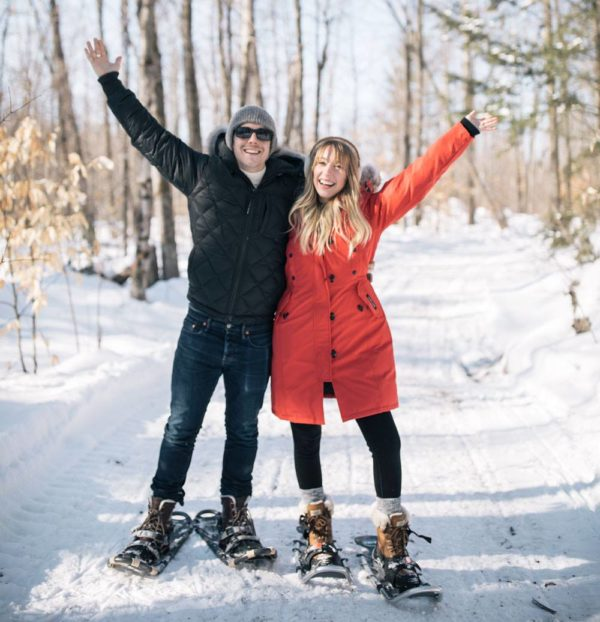couple on snowshoes with hands in the air