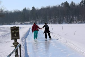 couple holding hands skating on the ice trail