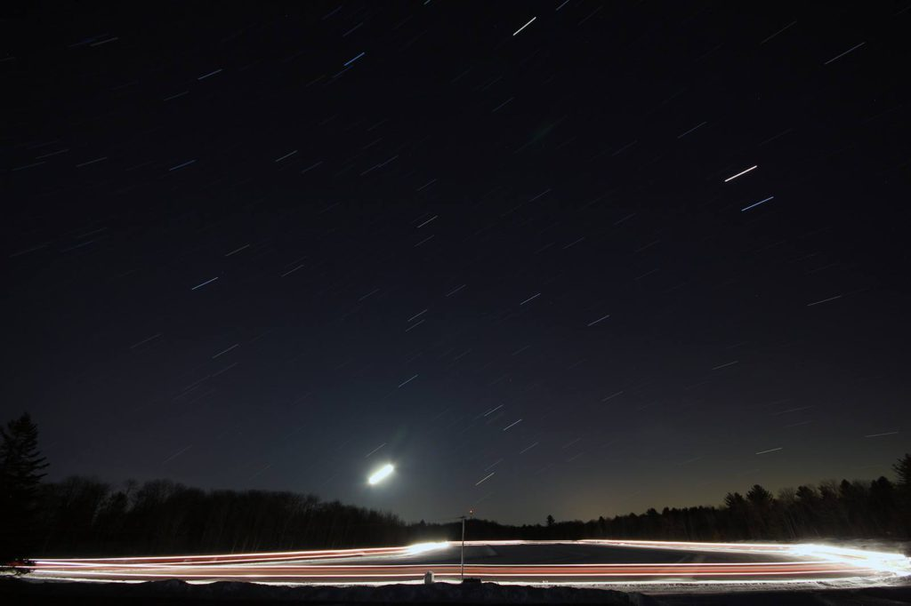 time lapse night photo showing light trails from equipment flooding the ice trail and star trails