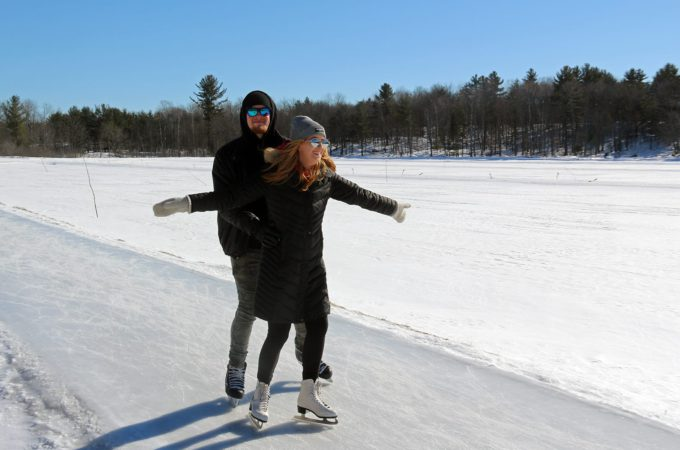 couple skating and girl has her arms out