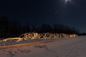 white corkscrew light trails going down the ice trail at night