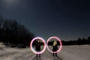 time lapse night photo with couple in skates surrounded by circular light trail