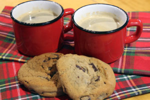 two mugs of coffee and two chocolate chip cookies