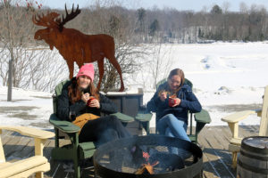 two girls eating chili from mugs outside in the winter by a fire