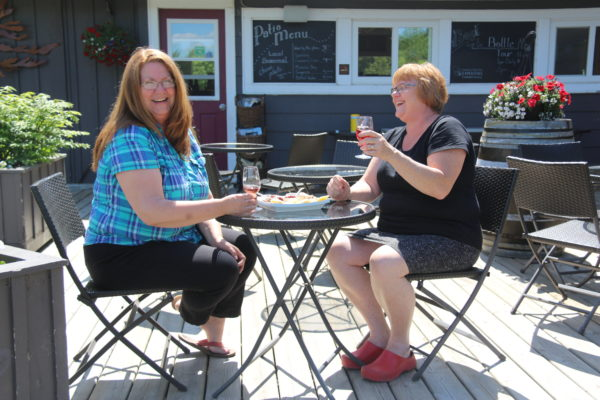 two smiling women with wine and cheese on a patio