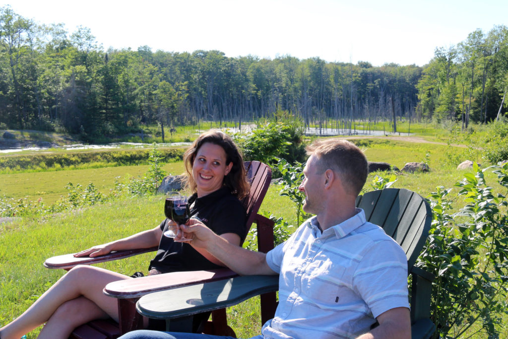 couple in Muskoka chairs toasting with wine glasses