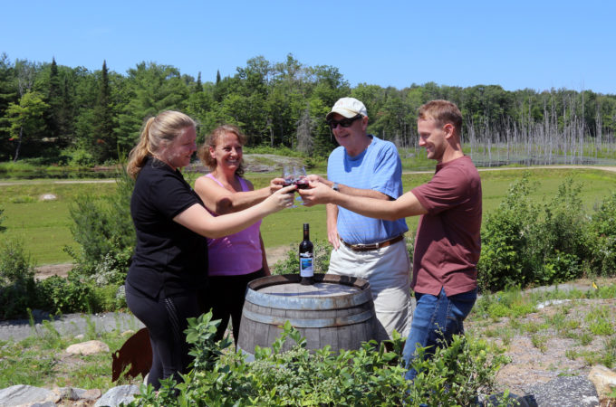 four smiling people around a wine barrel toasting with blueberry wine on top of blueberry hill