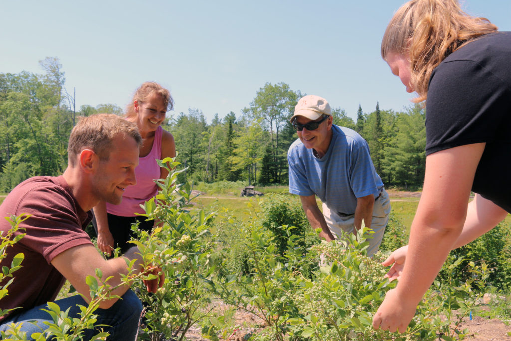 guide showing a group of smiling people blueberries growing on blueberry hill
