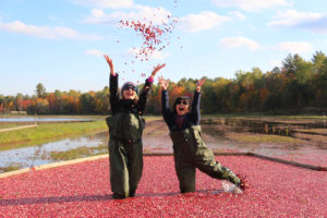 two women laughing as they toss cranberries in the air