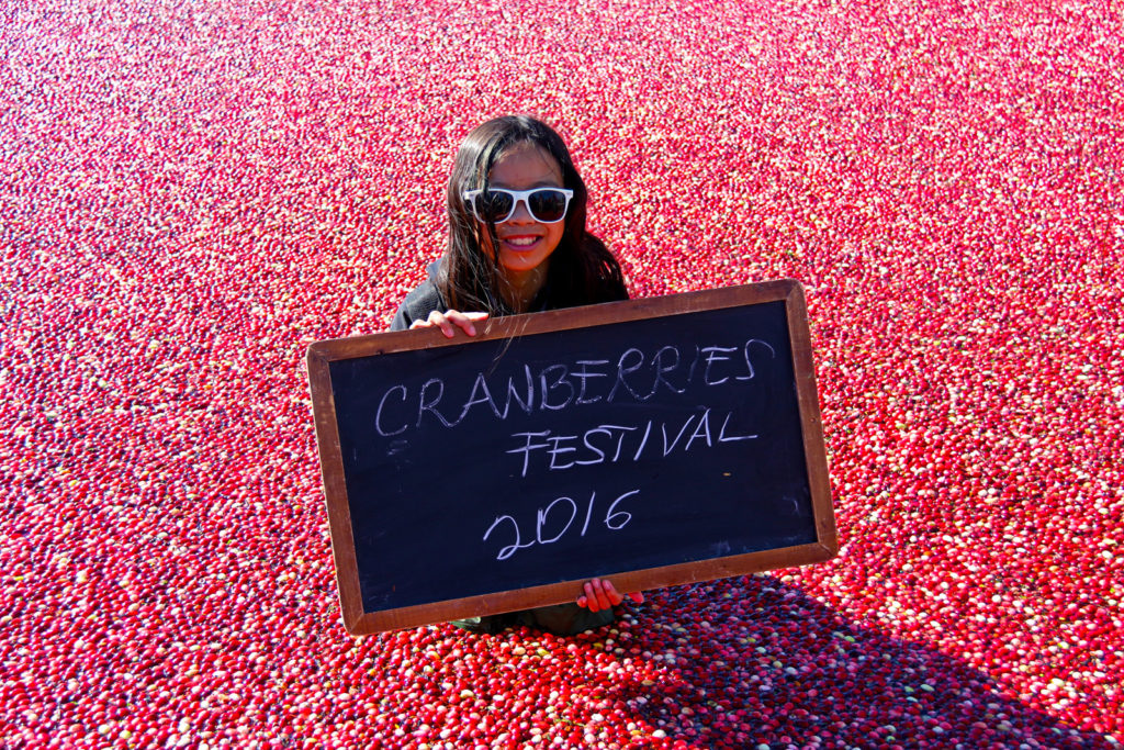 young girl surrounded by floating cranberries holding a sign