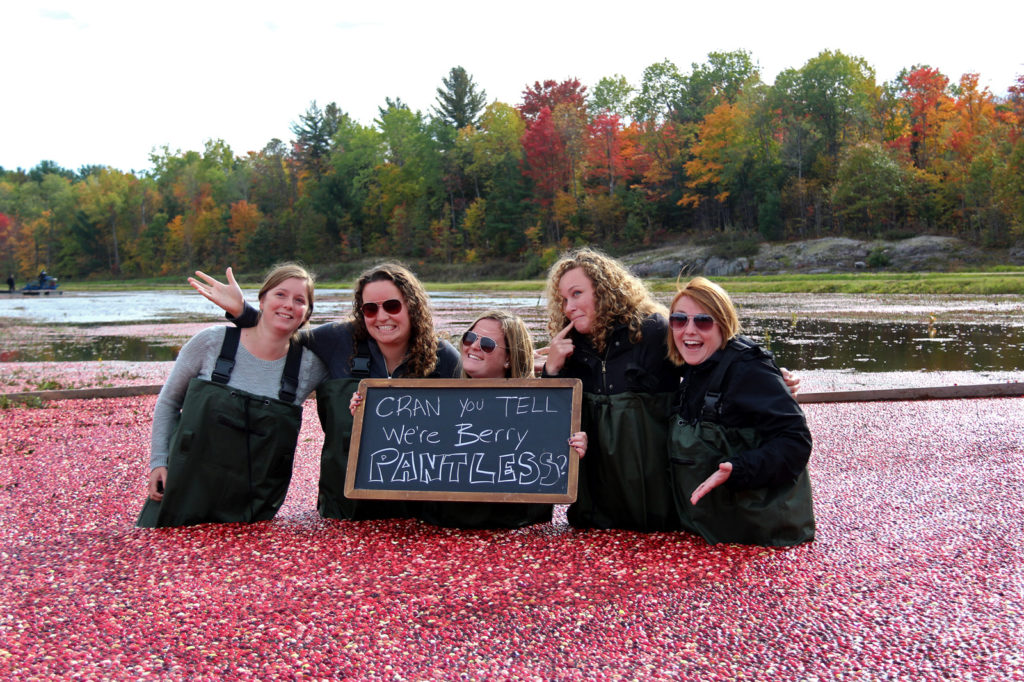five women kneeling in floating cranberries holding a sign