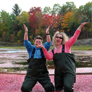 two women tossing cranberries in the air and laughing