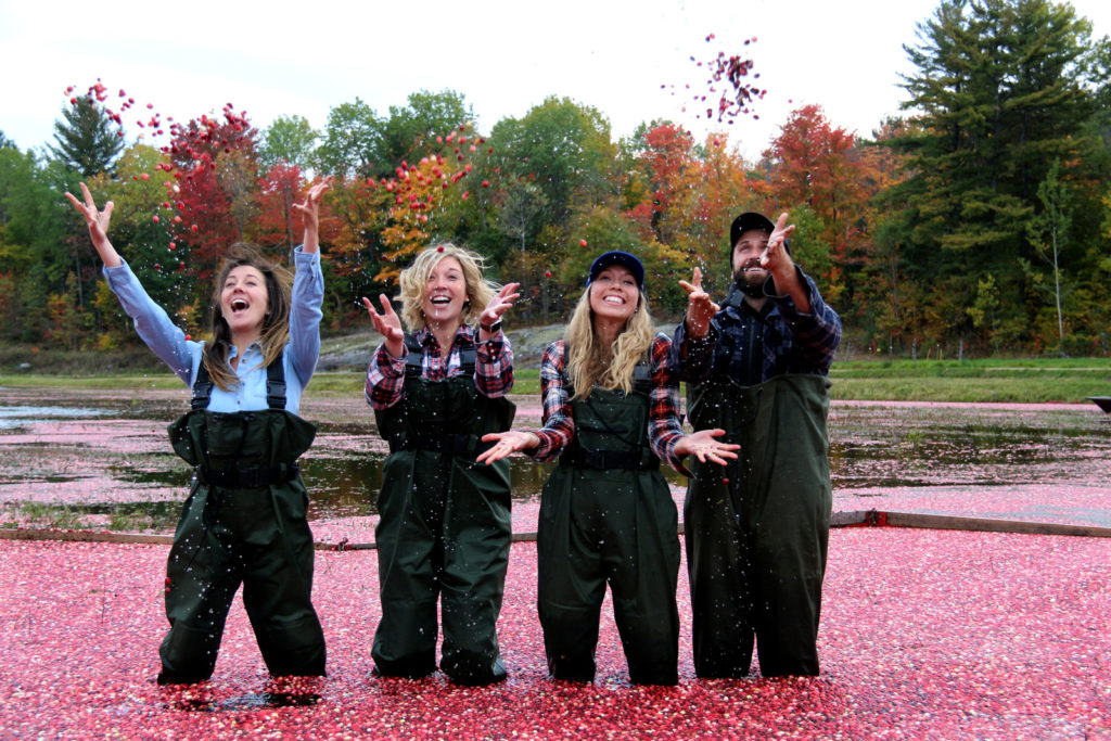 three women and a man laughing and throwing cranberries in the air