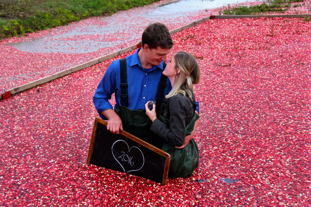 couple standing in floating cranberries after an engagement proposal