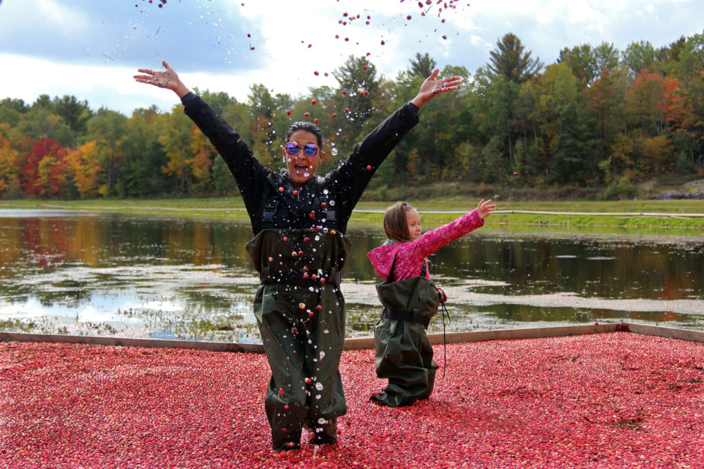mom and daughter throwing cranberries in the air and laughing