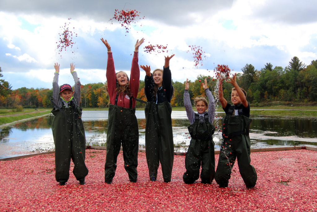 five kids laughing and tossing cranberries in the air
