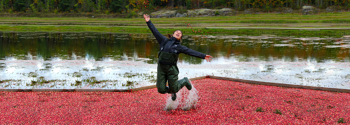 girl jumping out of floating cranberries