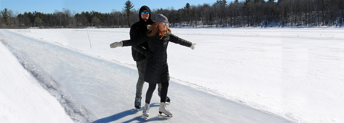 couple skating on outdoor ice trail