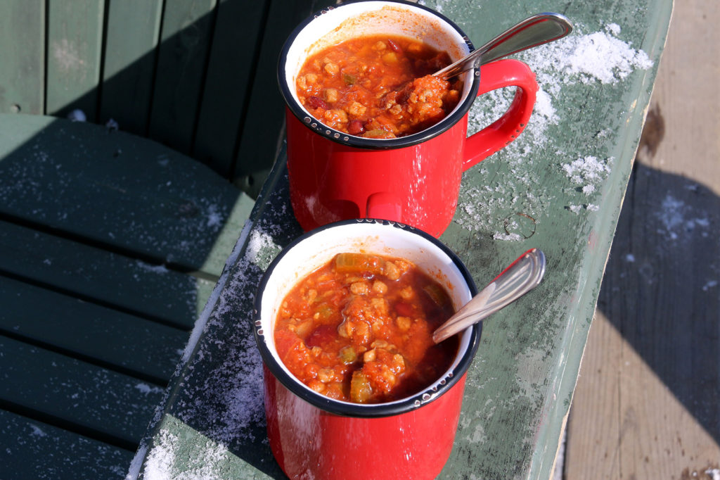 two red mugs of chili on a green muskoka chair