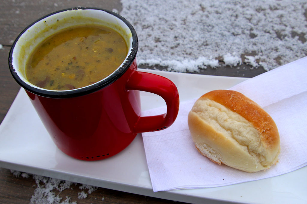 red mug of soup and a biscuit