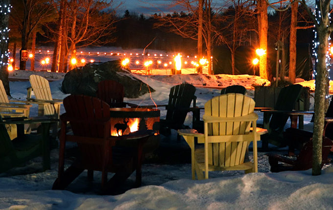 fire pit surrounded by muskoka chairs with the ice trail in the background lit up with torches for night skating