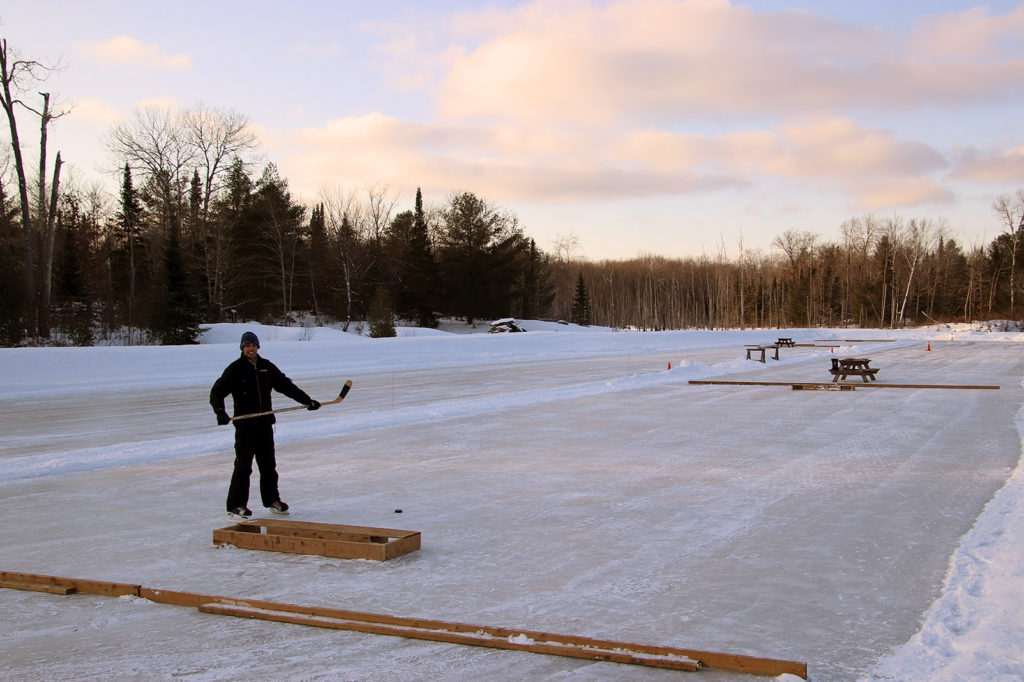 man standing on pond hockey rink with a hockey stick