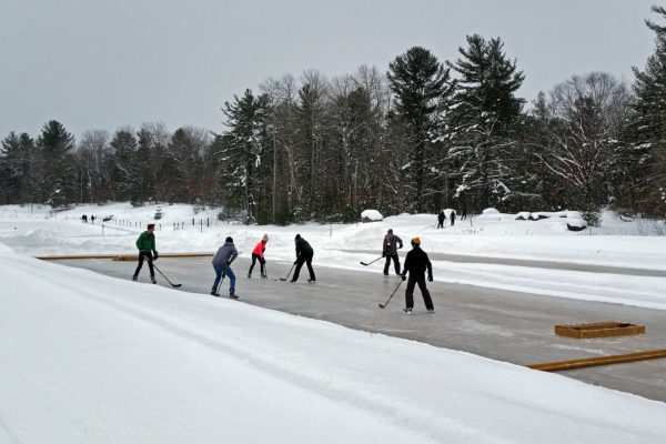 six people playing pond hockey on an outdoor rink