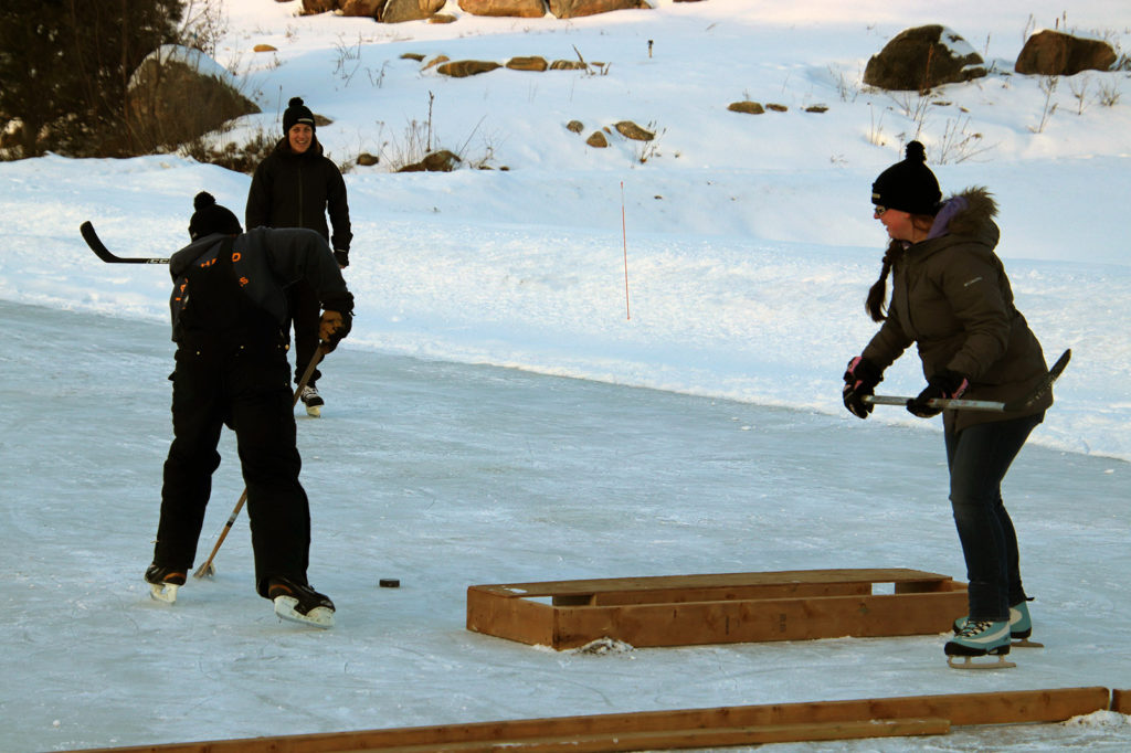 three people playing pond hockey on an outdoor rink