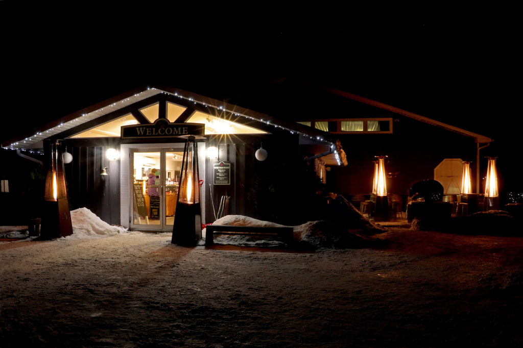 store at johnston's cranberry marsh and muskoka lakes winery lit at night in winter for night skating