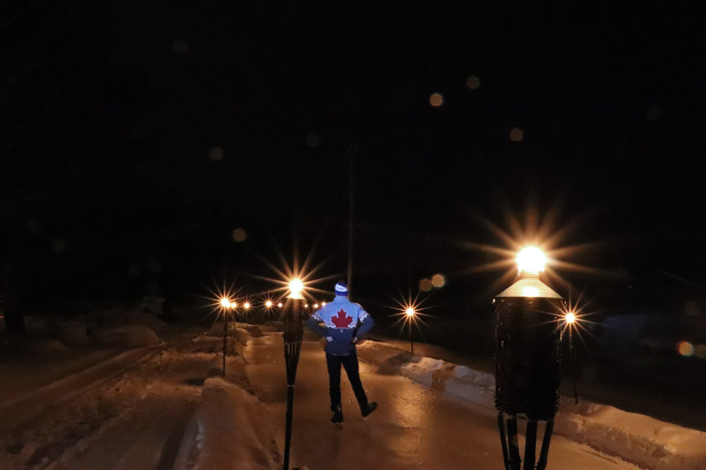 skater on an ice trail lit with torches for night skating