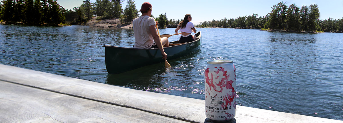 couple paddling canoe with can of spritzer on the dock behind them