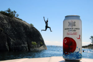 man jumping off cliff with can of cliff jump cranberry cider in the foreground