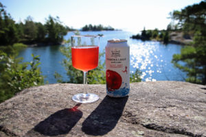 can beside a full glass of cliff jump cranberry cider overlooking a lake
