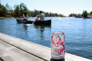 couple paddling a canoe with cranberry splash wine spritzer in the foreground on the dock