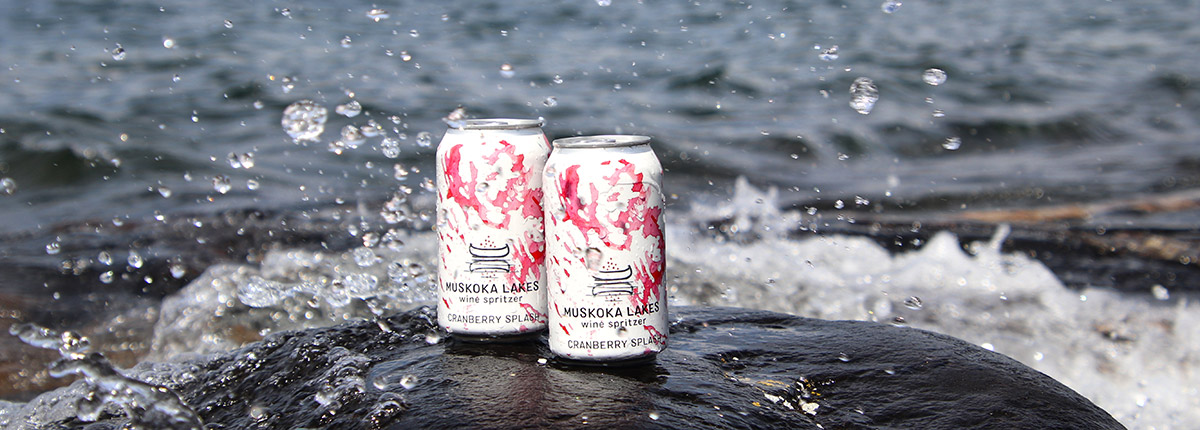 two cans of cranberry splash wine spritzer on a rock with splashing waves