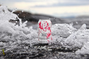can of cranberry splash wine spritzer surrounded by a wave