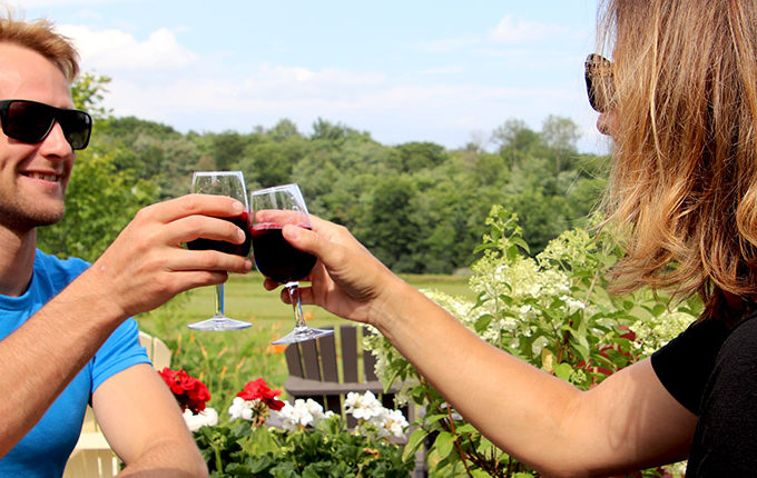couple clinking glasses on patio at muskoka lakes farm & winery in bala muskoka ontario