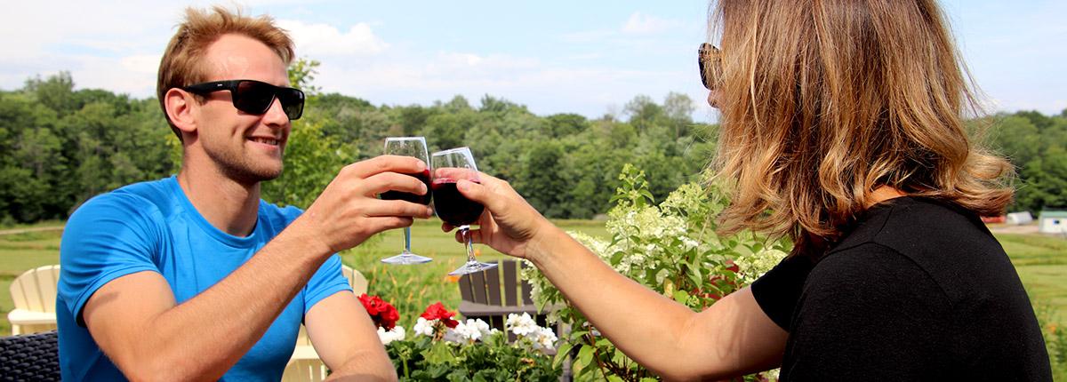 couple clinking glasses on patio at muskoka lakes farm & winery in bala muskoka ontario