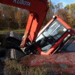 excavator sideways in a cranberry bog