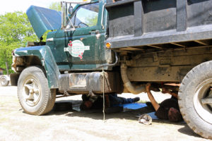 two guys lying under a truck fixing it