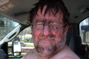 farmer's face covered in mud after falling in a ditch