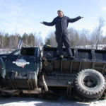 man standing on a truck sideways in a ditch