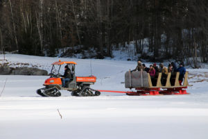 people in a sleigh being pulled by a tractor