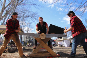 two men using a double buck saw to saw a cookie off a log in a log sawing contest