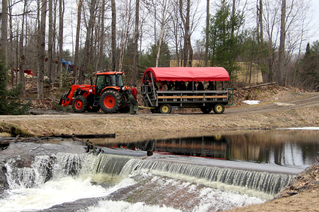 group of people on a tractor pulled wagon on a maple sugar bush tour