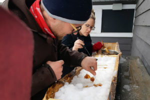 couple preparing maple taffy on snow