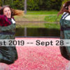 two girls jumping in floating cranberries wearing chest waders