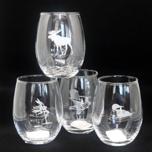 four stemless wine glasses with moose, tree, chair and loon etched on them